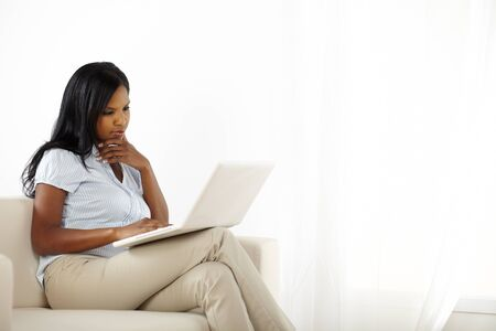 Portrait of cute young woman relaxing while reading on laptop at home photo