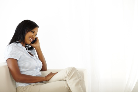 Portrait of a black young woman on mobile phone while resting at home photo