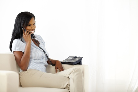 Portrait of a pretty black young woman talking on phone while resting at home photo