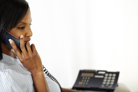 Portrait of a relaxed black young woman talking on phone while sitting at home photo