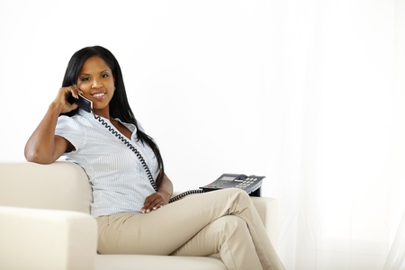 Portrait of a relaxed black young woman speaking on phone while sitting at home photo