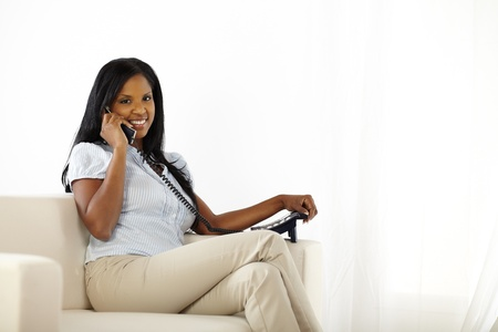 Portrait of a happy young female talking on phone and looking to you photo