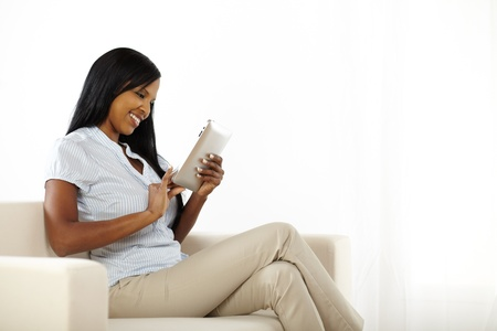 Portrait of a happy pretty young female using a tablet PC while resting on a sofa photo