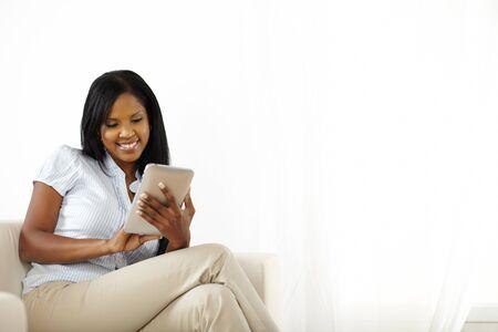 usando computadora: Retrato de una joven alegre, la lectura en un Tablet PC Foto de archivo
