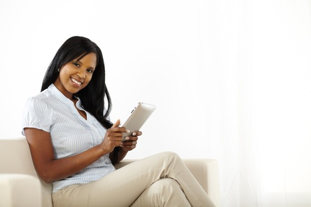 Portrait of a beautiful young woman using a tablet PC while smiling photo
