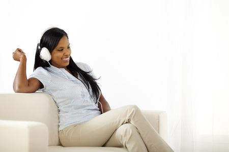 Happy young woman listening to music while having fun photo