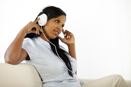 Lovely young woman listening to music while resting on light white background photo