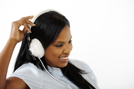 Close up portrait of a lovely young woman listening to music while smiling and looking down photo
