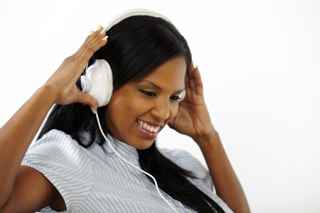 Close up portrait of a relaxed young woman listening to music while smiling and looking down photo