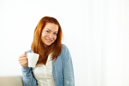 Portrait of a smiling girl enjoying a caffee cup photo