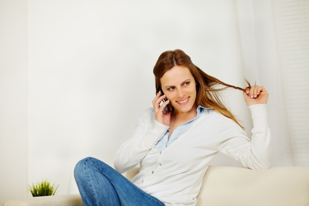 Close up portrait of a young pretty woman speaking on mobile phone at home photo