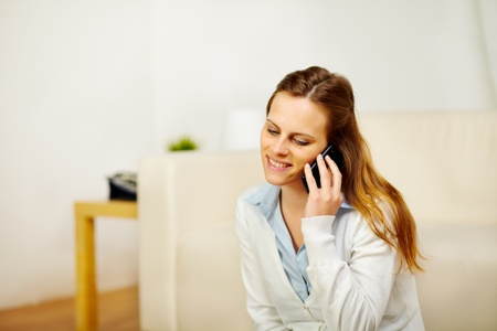 Portrait of a young relaxed woman talking on mobile phone photo