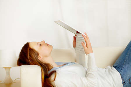 Portrait of a young lovely woman lying on sofa and kissing the laptop screen photo