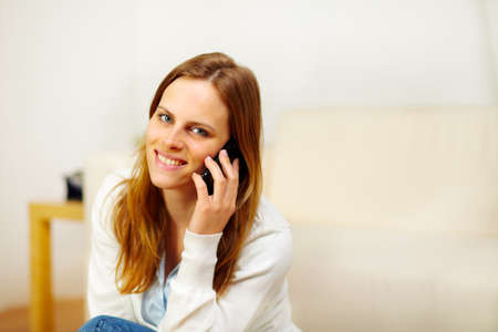Portrait of a young friendly beautiful girl speaking on phone and looking at you photo