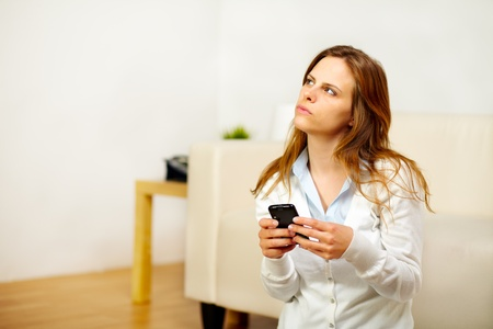 Portrait of a young woman making a call on the mobile phone while looking up photo