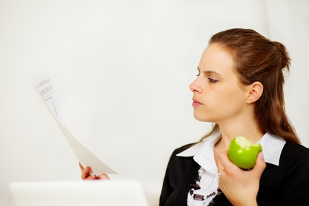 Portrait of a young business woman looking to a document while is eating a green apple photo