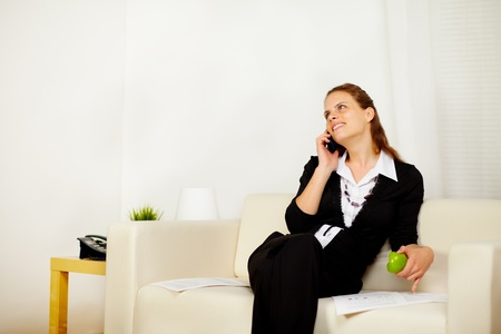 Portrait of a young business woman with a green apple and working while is on the phone and looking up photo