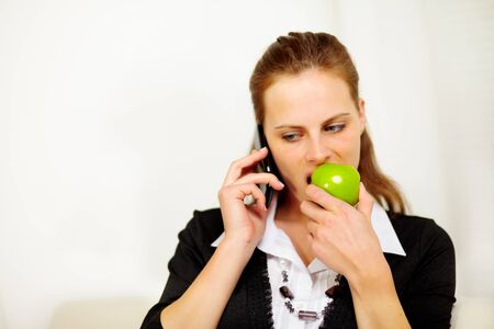 Close up portrait of a young businesswoman speaking on mobile phone while is eating a green apple photo