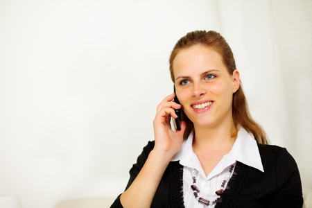 Close up portrait of a young friendly businesswoman on mobile phone and smiling photo