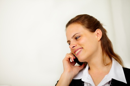 Close up portrait of a young businesswoman on cell phone and smiling photo