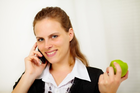 Close up portrait of a young businesswoman speaking on the mobile phone while is eating a green apple photo