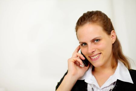 Close up portrait of a young beautiful smiling businesswoman on cellphone and looking to you photo