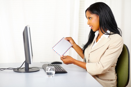 Portrait of a pretty businesswoman at work checking the mail on the computer screen photo