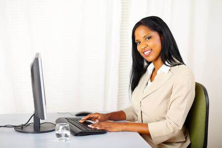 Portrait of a young beautiful businesswoman working on computer while looking to you photo