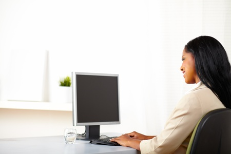 ethnic women: Portrait of a cheerful secretary looking to the monitor screen with copy space. Stock Photo