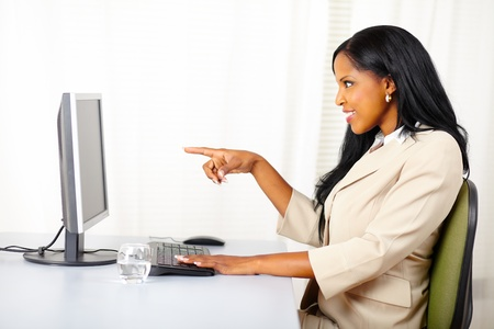 Portrait of a beautiful young businesswoman surprised while pointing the monitor screen photo