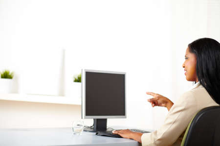 Portrait of a cheerful businesswoman looking  and pointing to the monitor screen with copy space. photo
