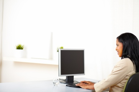 Portrait of a professional lady looking to the monitor screen with copy space while working. photo