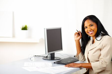 Portrait of a young businesswoman on work desk, smiling and looking to you