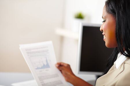 Portrait of a cheerful business woman reading documents photo