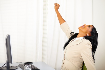 winning woman: Portrait of a successful executive female at work while celebrating victory
