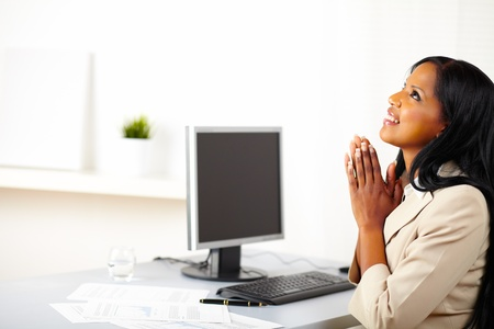 Portrait of a young businesswoman praying at work while looking up photo