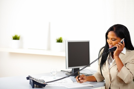 black secretary: Portrait of a young businesswoman on phone while working with documents