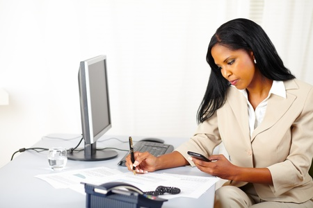 Portrait of a young businesswoman making a call while working on documents photo