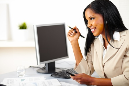 Portrait of a young beautiful executive female using a cellphone while looking up Stock Photo