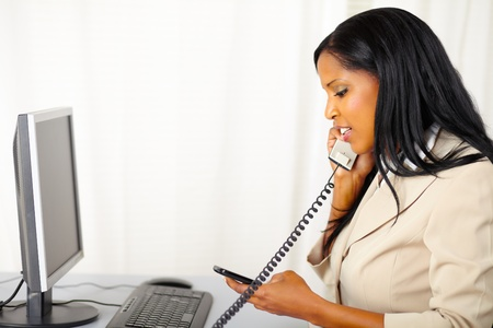 Portrait of a young professional woman talking on phone while use a mobile phone at work photo
