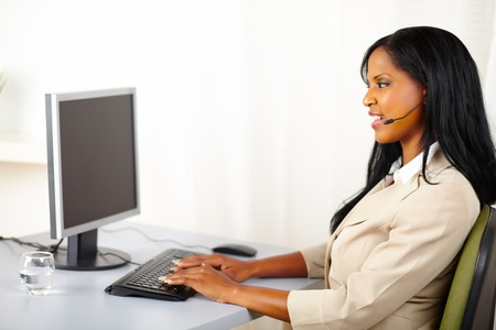 Portrait of a professional callcenter operator working on computer photo