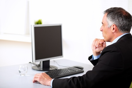 Portrait of a senior businessman working on computer at the office. photo