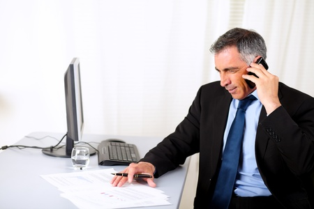 Potrait of a attractive businessman speaking on mobile at the office Stock Photo