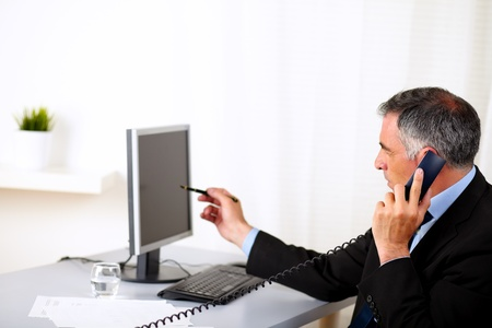 Portrait of a elegant businessman pointing the computer screen at the office Stock Photo