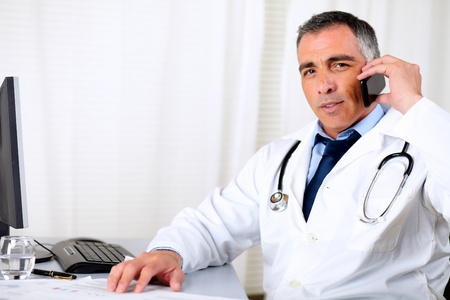 doctor computer: Portrait of a professional friendly senior doctor using a mobile phone