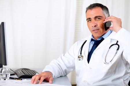hablando por telefono: Retrato de un profesional m�dico jefe amigable mediante un tel�fono m�vil
