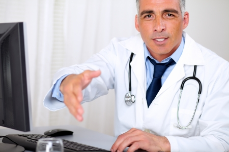 Portrait of a senior trustworthy doctor in from the computer while greeting and looking to you photo