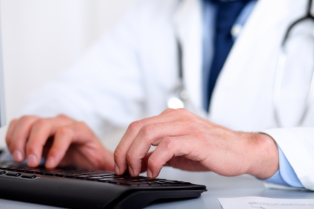 Portrait of doctor hands on keyboard while using the computer at hospital workplace photo