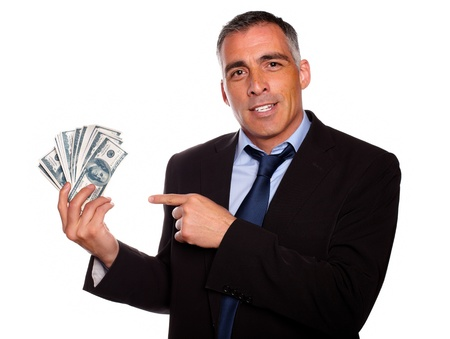 man holding money: Portrait of a hispanic senior business man holding and pointing  cash dollars on isolated background