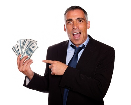 Portrait of excited executive holding and pointing cash money on isolated background Stock Photo